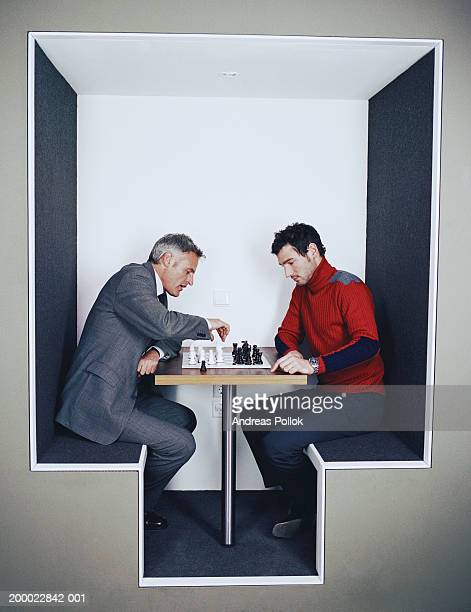 Two businessmen at table playing chess
