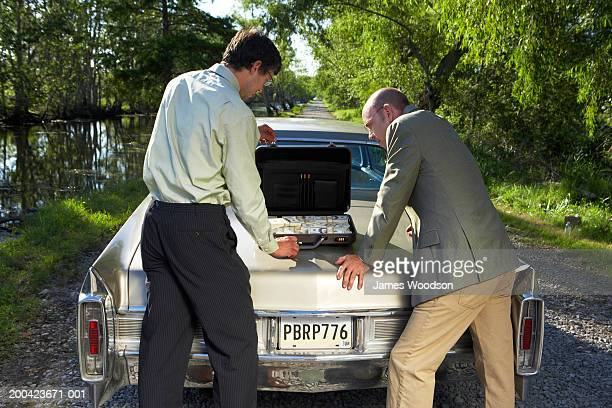 Two businessmen behind car with money in briefcase, rear view
