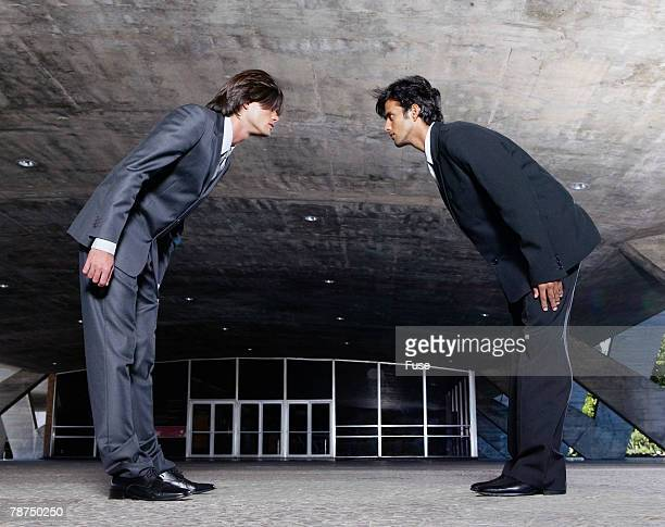 Two Businessmen Bowing in Front of Office Building