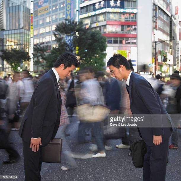 Two businessmen bowing