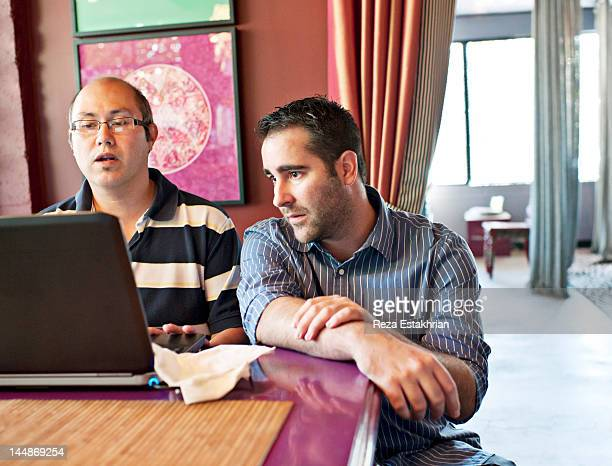Two businessmen check information on computer