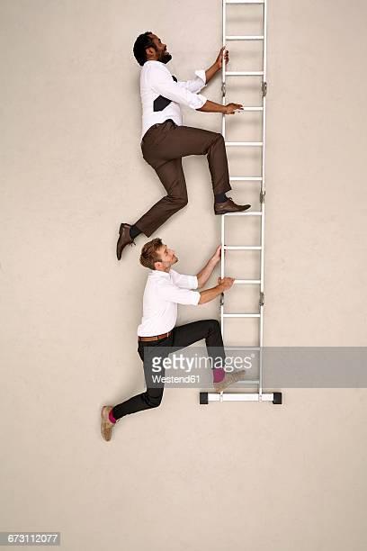 Two businessmen climbing ladder