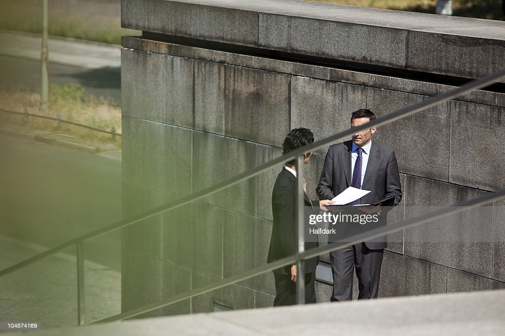 Two businessmen conducting suspicious business : Stock Photo