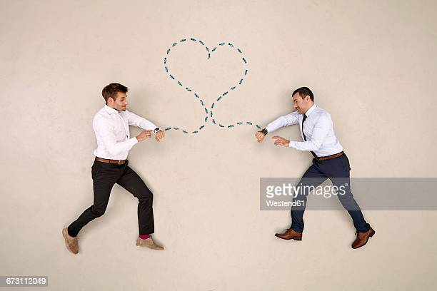 Two businessmen connected via smartwatch and heart-shaped dotted line