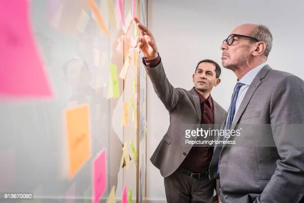 Ein Geschäftsmann deutet auf Notizzettel an einer transparenten Tafel und der andere schaut interessiert zu