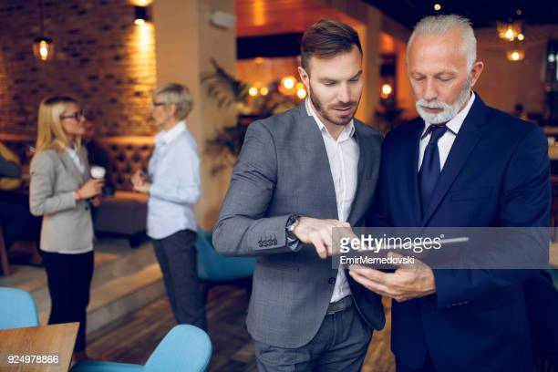 Two businessmen discussing business using digital tablet in cafe