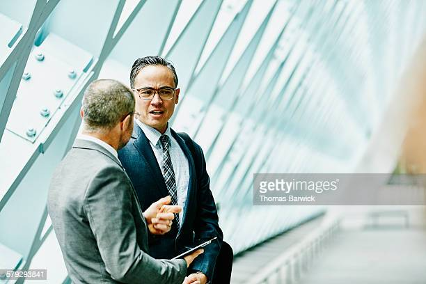 Two businessmen discussing data on digital tablet