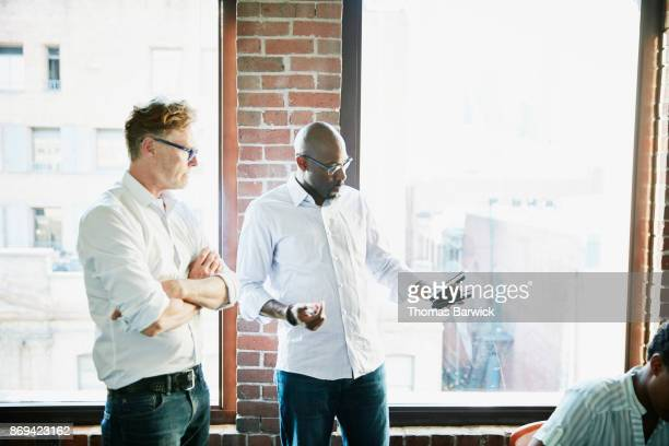 Two businessmen discussing data on smartphone during meeting in high tech office conference room