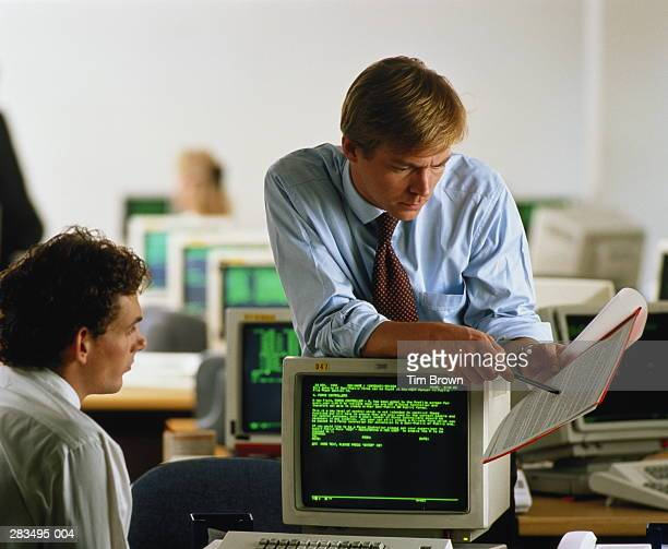 Two businessmen discussing document over computer terminal in office