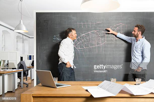Two businessmen discussing drawing at blackboard