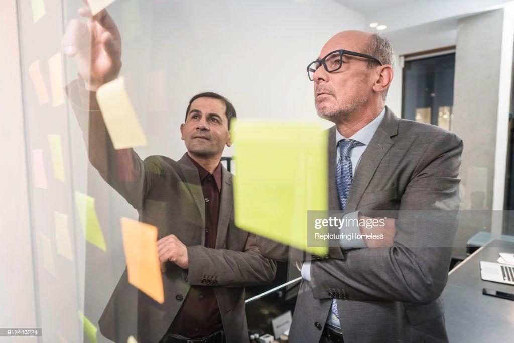 Zwei Geschäftsmänner diskutieren an einer transparenten Tafel : Stock-Foto