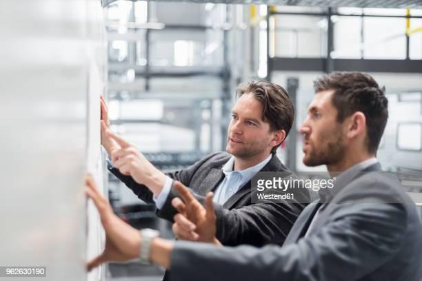 two businessmen discussing plan in modern factory - ingenieur stock-fotos und bilder