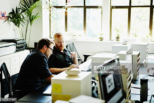 Two businessmen discussing project at workstation