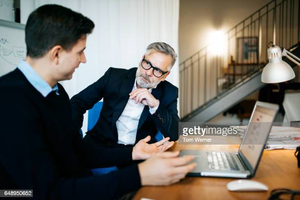 Two businessmen discussing the latest project on a computer