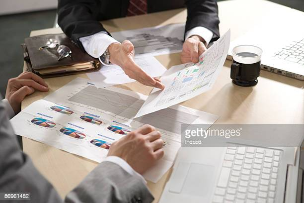 Two businessmen discussing with document in office