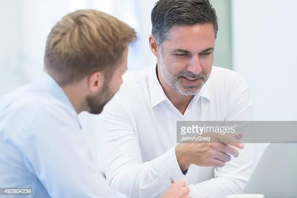 Dos empresarios discutiendo trabajo y utilizando latop