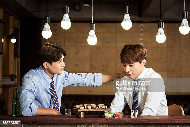 Two Businessmen Drinking Soju (Korean Vodka) at Sushi Restaurant