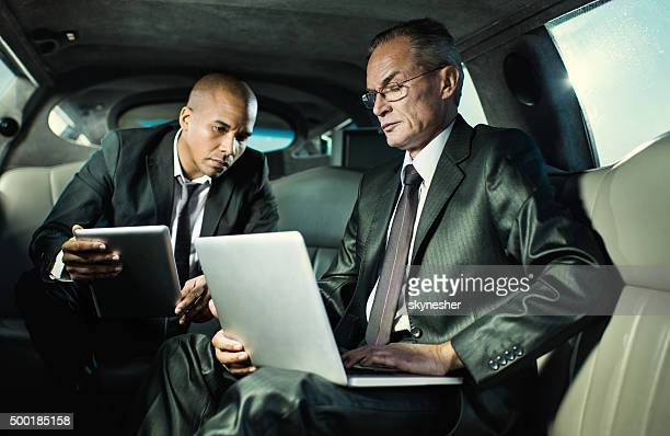 Two businessmen driving to work and using wireless technology.
