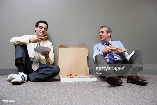 Two Businessmen Eating Pizza on Floor