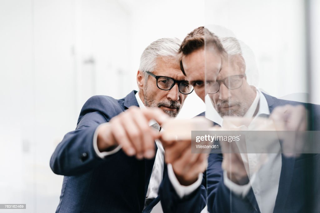 Two businessmen examining architectural model at glass pane : Stock-Foto