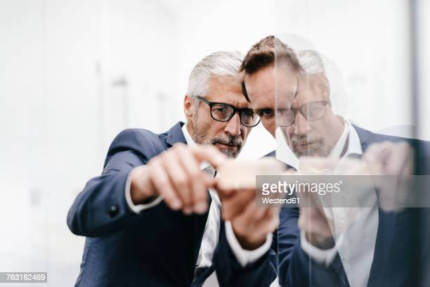 two businessmen examining architectural model at glass pane - glas materiaal stockfoto's en -beelden