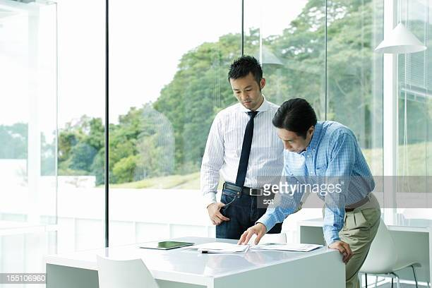 Two businessmen examining plans at desk in office