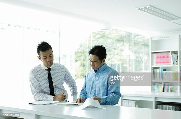 Two businessmen examining plans in office