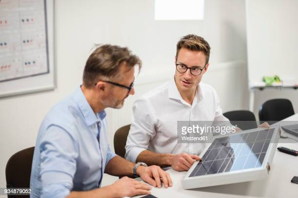 two businessmen examining solar panel on desk in office - energieindustrie stock-fotos und bilder