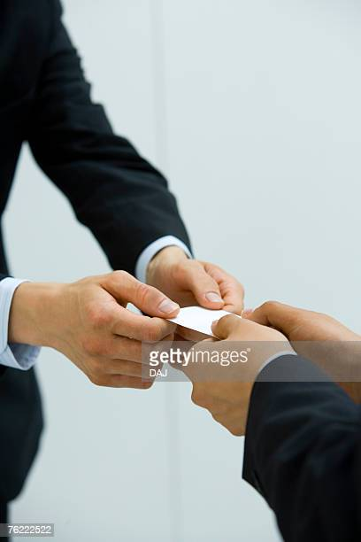 Two businessmen exchanging a business card, high angle view, white background