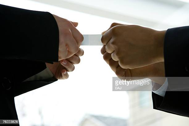 Two businessmen exchanging a business card, low angle view, side view, close up
