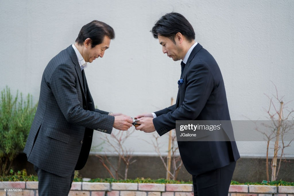 Two businessmen exchanging business cards outdoors stock photo two businessmen exchanging business cards outdoors stock photo reheart Image collections