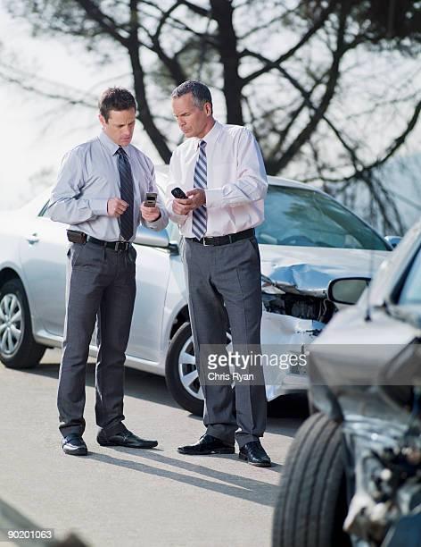 Dos ejecutivos intercambiando información sobre coches dañado