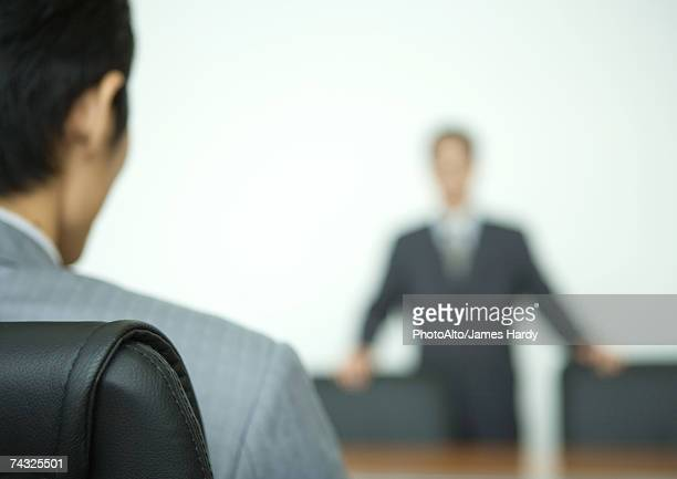 Two businessmen facing each other across conference table, focus on foreground