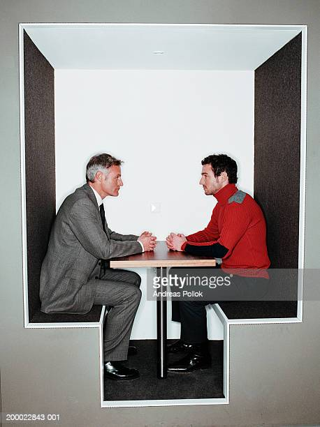 Two businessmen facing each other over table, profile