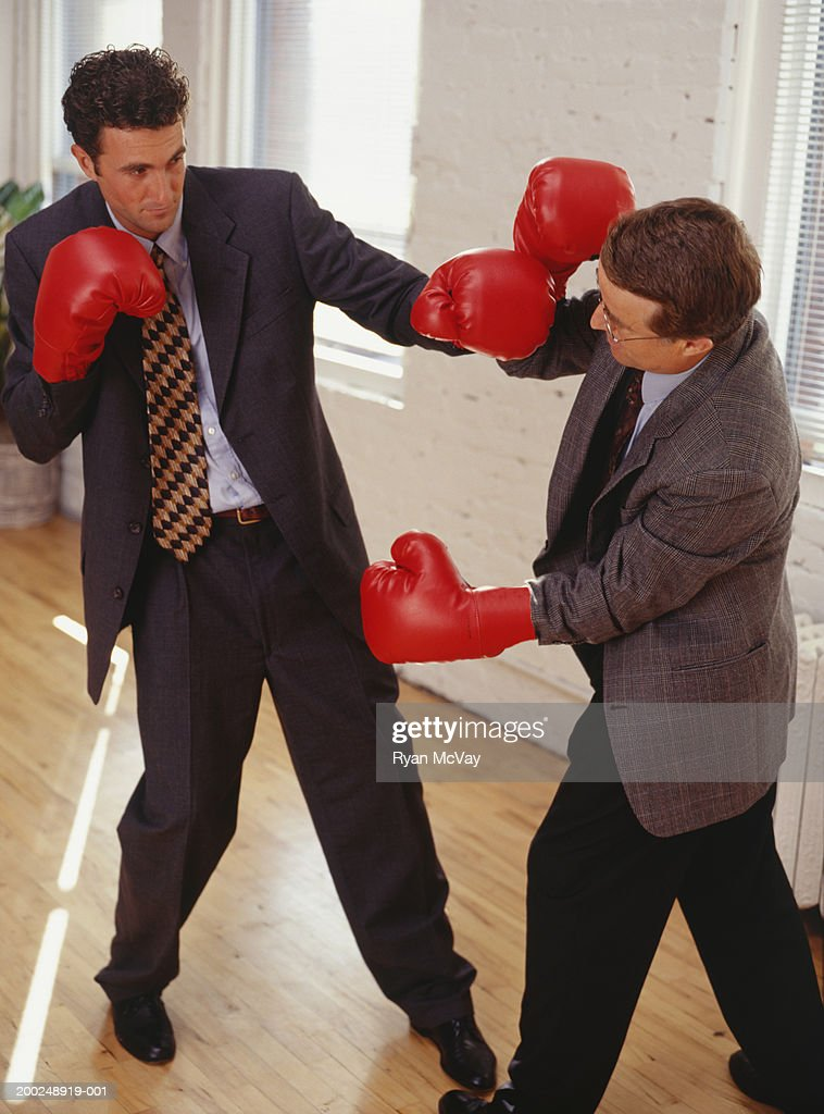 Two Businessmen Fighting In Empty Room Wearing Boxing ...
