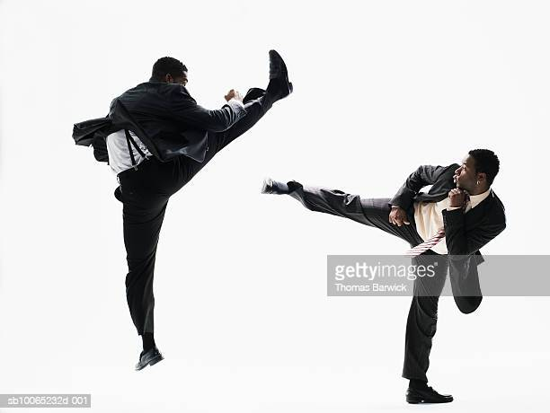 Two businessmen fighting on white background