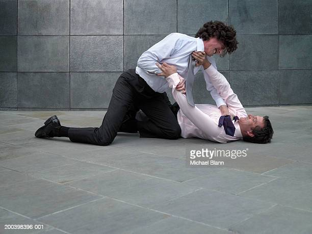two businessmen fighting, younger man grabbing colleague's tie - violence ストックフォトと画像
