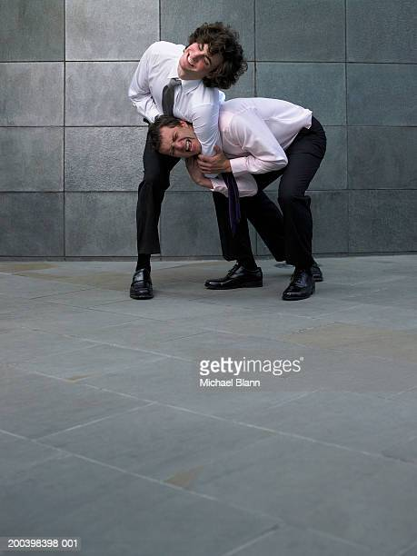 Two businessmen fighting, younger man holding colleague in headlock