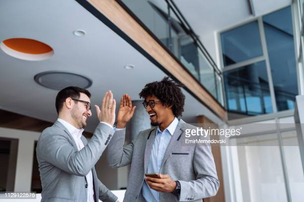 two businessmen giving each other high-five - high five stock pictures, royalty-free photos & images