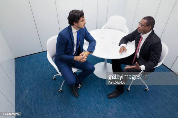 two businessmen have discussion in office meeting room - navy blue stock pictures, royalty-free photos & images