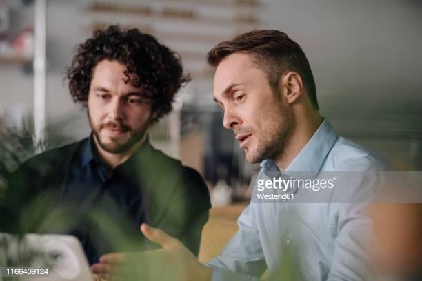 two businessmen having a meeting in a coffee shop - beratung stock-fotos und bilder