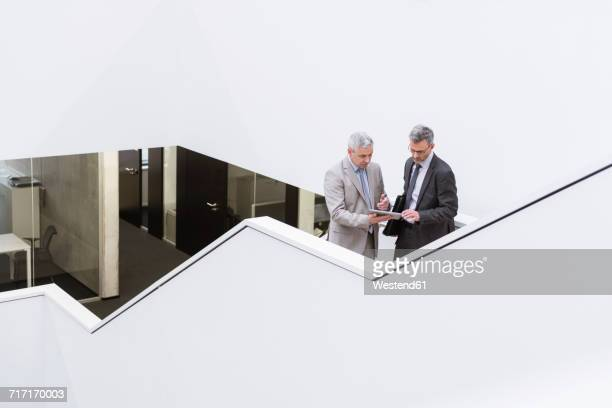 two businessmen having an informal meeting, using digital tablet - man made structure stock pictures, royalty-free photos & images
