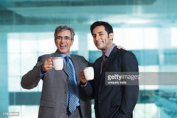Two businessmen having coffee and smiling