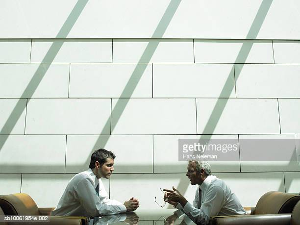 Two businessmen having discussion in hotel lobby, side view