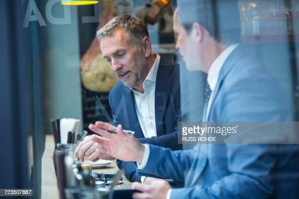 two businessmen having discussion in restaurant window seat - lunch break stock photos and pictures