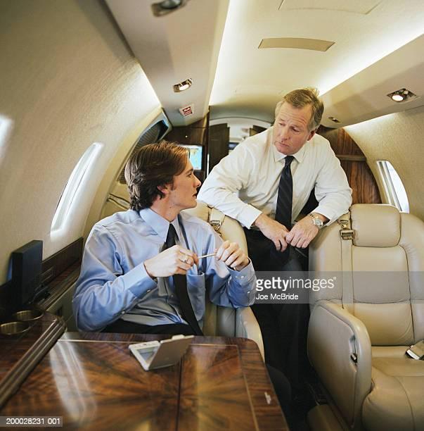 two businessmen having meeting on corporate jet - voertuiginterieur stockfoto's en -beelden