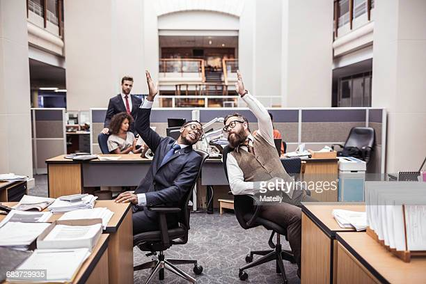 Two businessmen high-fiving in office