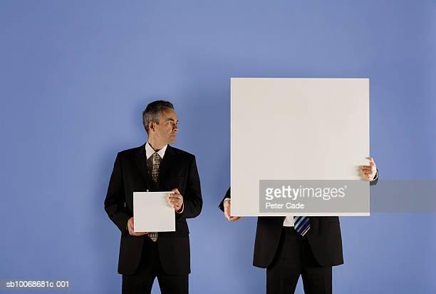 two businessmen holding boxes - fianco a fianco foto e immagini stock