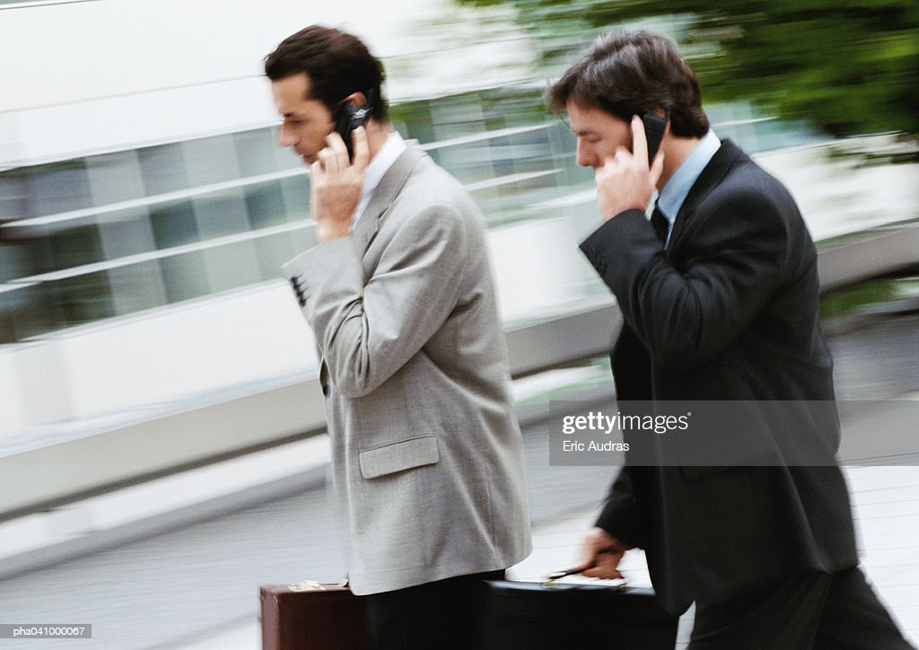Two businessmen holding briefcase and cell phone, walking outside : Stockfoto