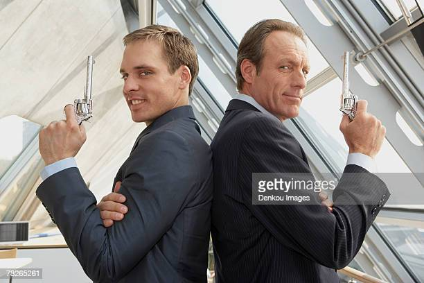 Two businessmen holding revolvers and standing back to back